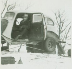 "1930-something Ford with V-8 engine, damaged in an accident, powered the rope tow. Note the extra wheel/tire mounted on the rear to allow the rope to ride in between. When a skier grabbed the rope, the man behind the wheel ""gave it some gas"" to get them up the hill."